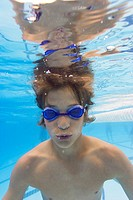 underwater lifestyle shot of a teenage male in goggles as he swims in a pool