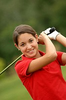 Front view of a teenage girl playing a golf shot