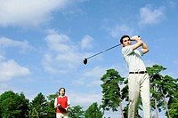 Man hitting a golf shot with a woman looking on