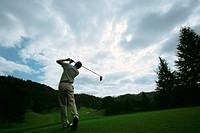 A man swings a golf club against a dramatic sky