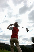 Rear view of a woman in action playing golf in the golf course