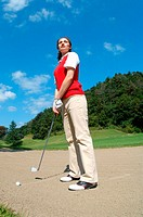 Woman contemplating before playing a bunker shot