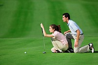 Couple lining up a putt on the green