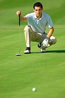Man lining up a putt on the green
