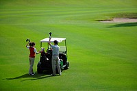 Couple putting their golf clubs into their golf bags on a golf cart