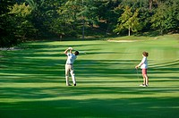 Male golfer hitting down the fairway as a woman looks on