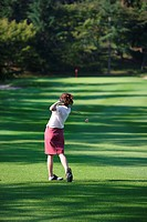Rear view of a female golfer playing a shot