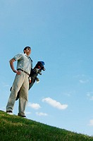Low angle view of a man carrying a golf bag