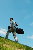 Male golfer walking purposefully