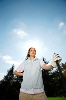 Low angle view of a female golfer on a sunny day