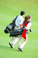 Couple carrying golf bags walking down the fairway