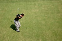 Side view of a male golfer playing a shot