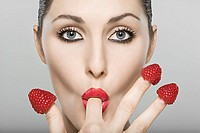 Woman with a raspberry on the end of each finger