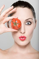 Woman holding tomato over eye