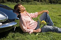 Man relaxing by car in field