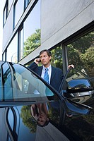 Businessman on cell phone by car