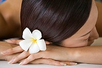 Woman with flower in hair lying down (thumbnail)