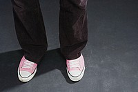 Feet of person wearing pink trainers
