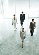 Four executives walking through office building lobby