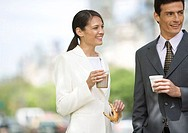 Businesswoman and man standing, having coffee outdoors
