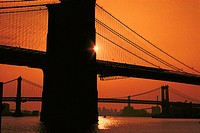 Sun rising behind the Brooklyn Bridge and another bridge, NYC, USA