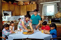 A Native American Indian family sharing food in the kitchen.