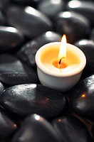 Single candle arranged with stones