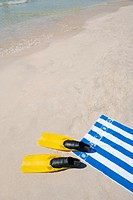 Beach towel and flippers on the beach