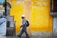 Picture from a man walking in front a painted wall. Antigua Guatemala. Sacatepéquez Region. Guatemala