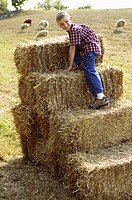 Boy climbing a stack of hay bales (thumbnail)