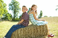 Boy and girl sitting on top of a hay bale (thumbnail)