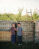 Two boys eating apples in front of a fence (thumbnail)