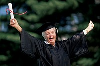 Older woman with diploma, cap, and gown.