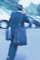 Man walking with luggage and talking on cellphone, motion blur.