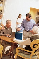 Man training seniors at assisted living facility to use computers.