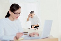 Woman ordering online, man talking on telephone, blurred.