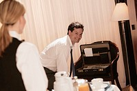 Businessman in hotel room receiving room service.