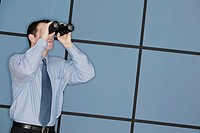 Businessman looking through binoculars.