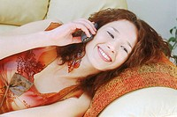 Portrait of Young Woman Lying Down and Talking on Mobile Phone