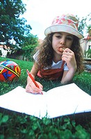 Young girl lying down writing in a book