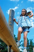 Young girl walking on a wooden log