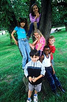 Young children at a tree in the park