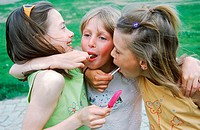 Three young girls licking lollipops with their arms around each other