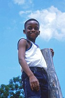 Young boy standing against a wooden pole smiling