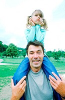 Portrait of a father carrying daughter on his shoulders