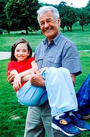 Portrait of grandfather carrying his granddaughter in his arms (thumbnail)