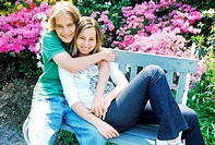 Portrait of young couple lying on a garden bench
