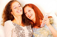 Two young women laughing and holding a mobile phone (thumbnail)