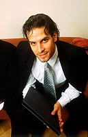 Young businessman sitting holding a file
