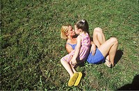 High angle view of mother and daughter lying down on grass kissing
